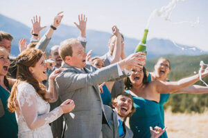Wedding party pops champagne to celebrate in Colorado mountains