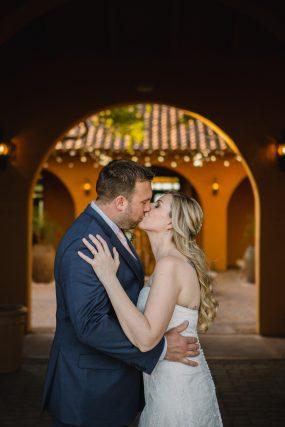 Phoenix wedding photograph of couple kissing under arch