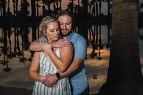 Phoenix wedding photograph of engaged couple hugging with palm trees
