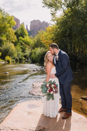 Phoenix wedding photograph of groom kissing bride on river
