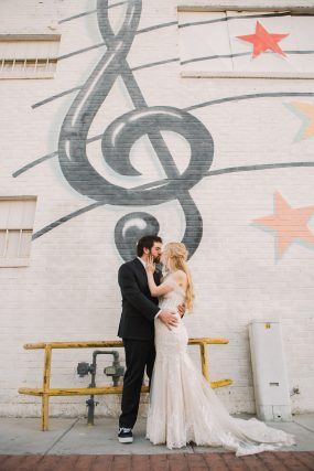 Phoenix wedding photograph of couple kissing in front of mural
