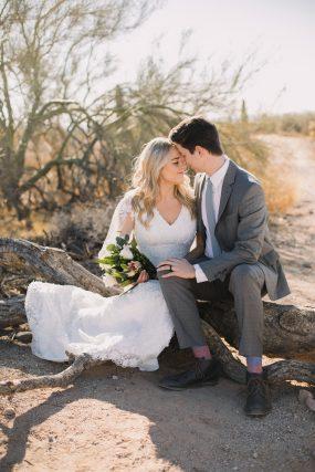 Phoenix wedding photograph of couple sitting on log hugging